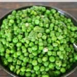 Peas with green onions and basil in a serving bowl.
