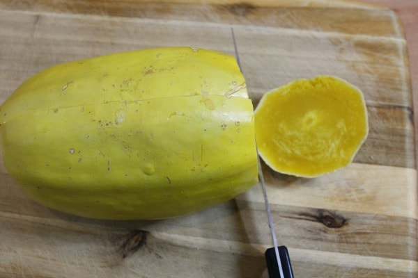 Cut the end of the cooked spaghetti squash off and cut the squash in half.