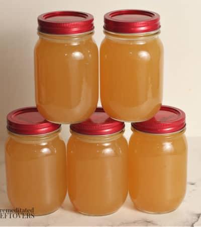 Mason jars of homemade turkey broth made in a crock pot