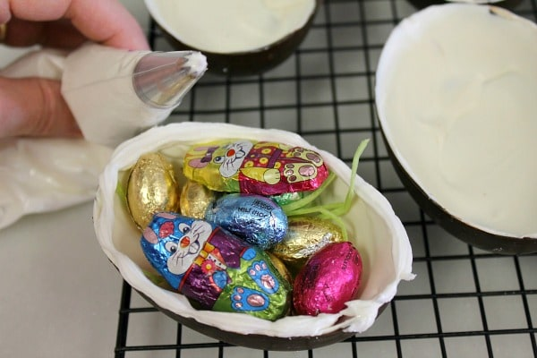 Fill the bottom half of hollow chocolate eggs then pipe icing on edge