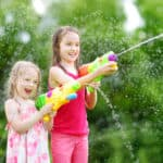 little girls playing with water guns on hot summer day. Cute children having fun with water outdoors.