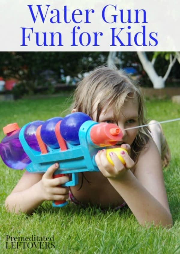 A girl laying on the lawn squirting a water gun.