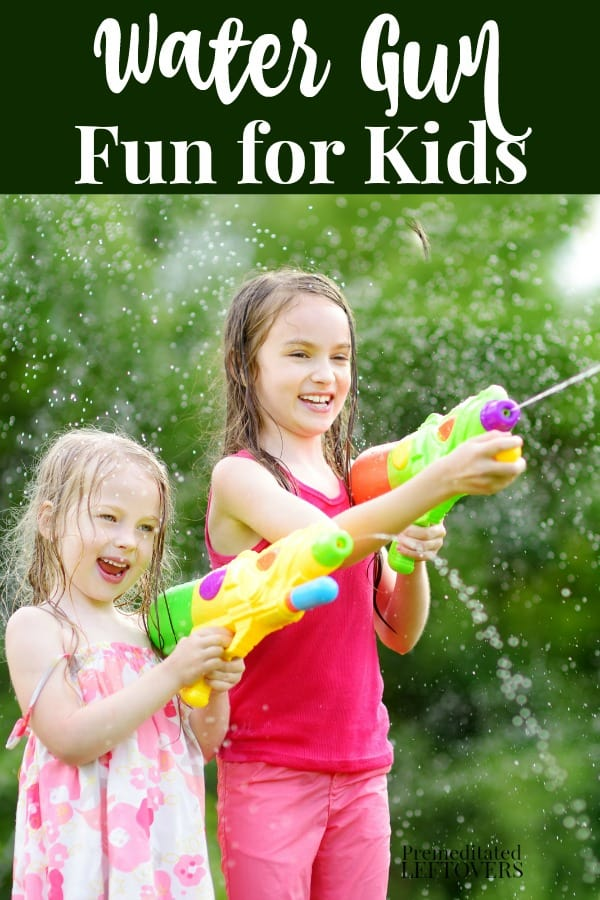 2 kids playing with water guns in the backyard