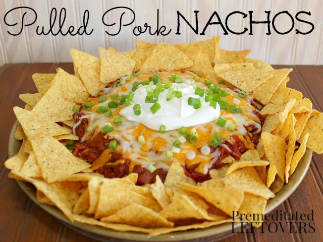 Pulled Pork Nachos topped with cheese, sour cream and green onions.