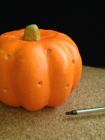 Use a screw driver to make the holes for the light to shine through foam pumpkin