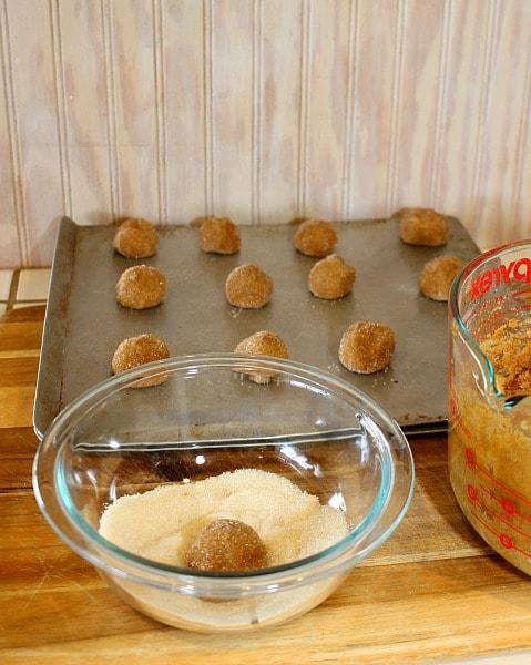 rolling low-sugar molasses cookie dough in sugar before baking