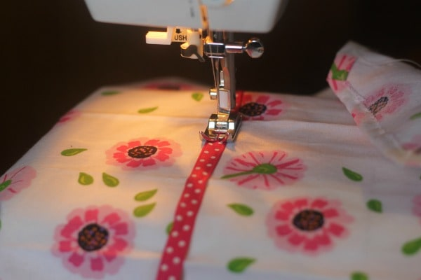 Sewing ribbon on children's dish towel apron