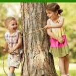 boy and girl playing with sticks by tree -