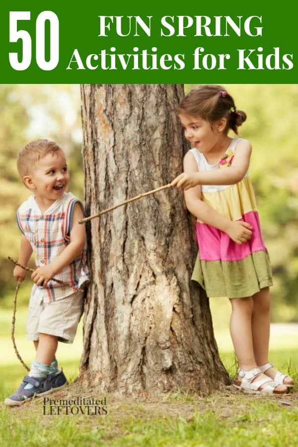 boy and girl playing with sticks by tree