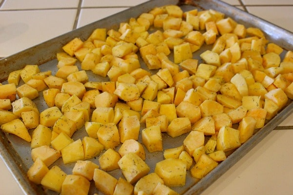 Toss Cubed Acorn Squash with Rosemary and Garlic on baking sheet. Then roast acorn squash.