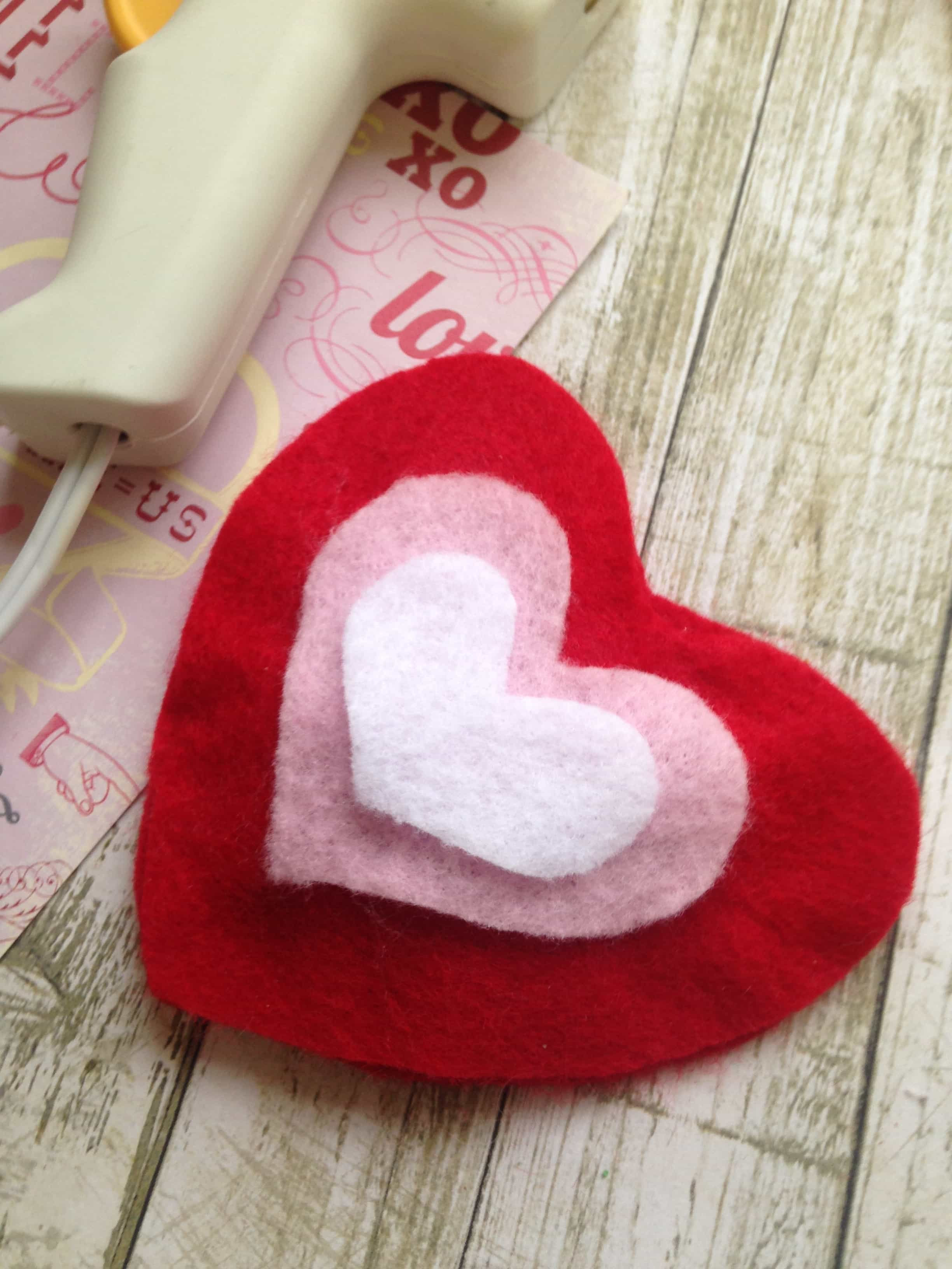 Use a glue gun to seal the heart and attach additional felt hearts on top of the felt heart sachet