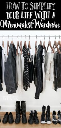 A minimlist wardrobe consisting of black and white clothes on a rod and shoes on a wooden floor.