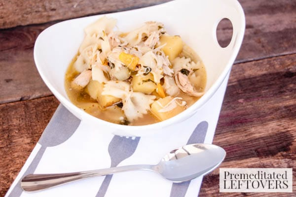 Best Homemade Chicken Soup with Bowtie Pasta- serving of soup in a bowl with spoon