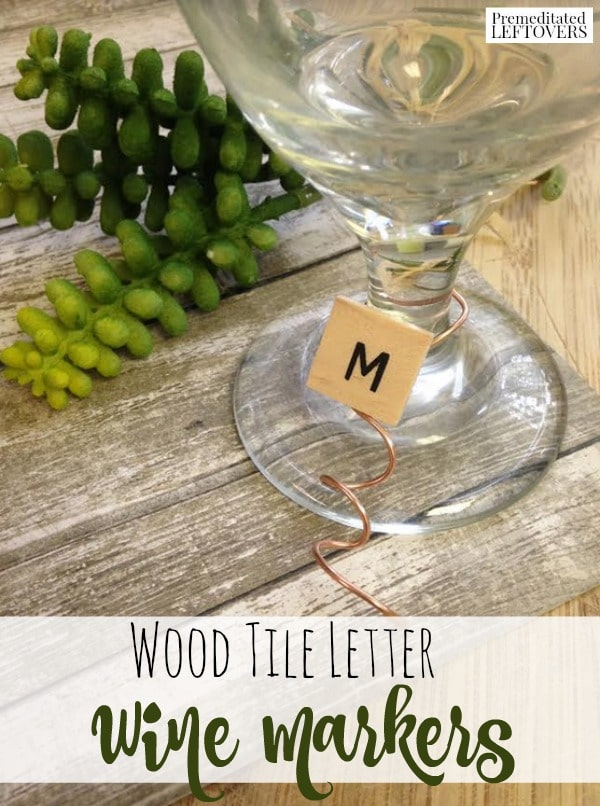Wood Tile Letter Wine Markers attached to the stem of a wine glass with copper colored wire - These simple DIY wine markers use upcycled tile letters to create something truly unique for your next party or wedding!
