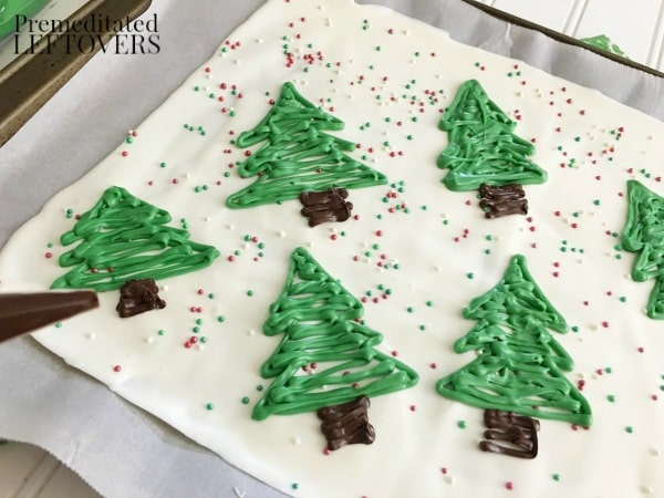 Quick and Easy Christmas Tree Candy Bark Tutorial - Add the trunks by piping dark chocolate at the base of the trees.