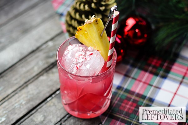 Raise a glass of Christmas cheer! This simple Cranberry, Pineapple, and Peppermint Cocktail recipe is garnished with crushed candy cane and pineapple.