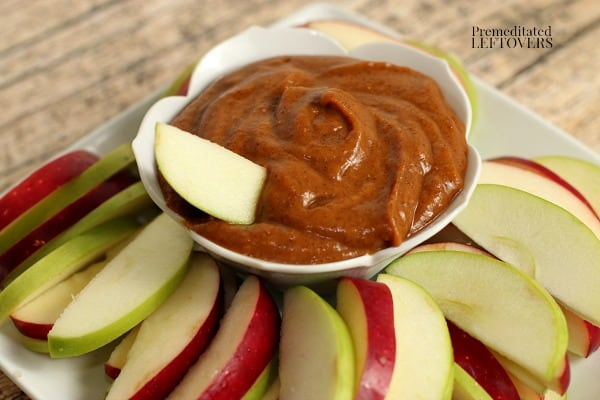 A bowl of healthy pumpkin dip with sliced apples for dipping.