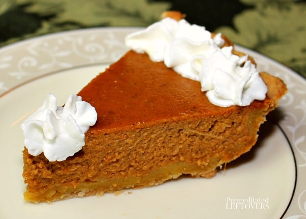 a slice of homemade pumpkin pie topped with whip cream.