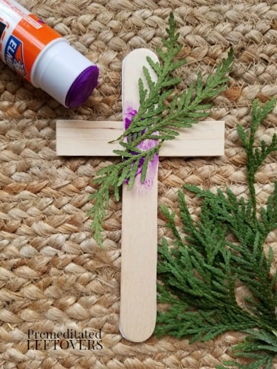 Glue the greenery and twine to the back of the cross.
