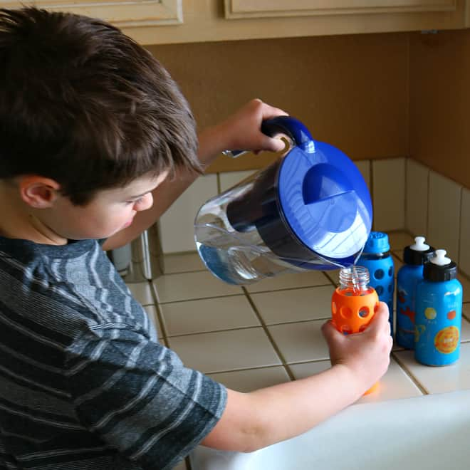 Son filling water bottles with filtered water from Brita Filter Pitcher