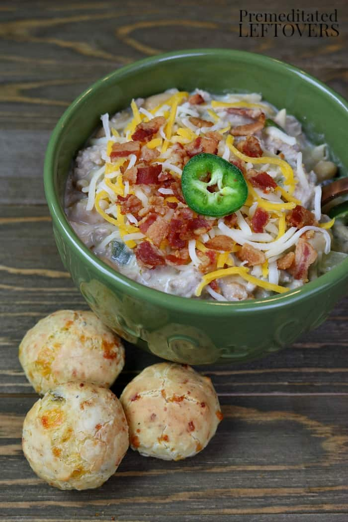 A bowl of Jalapeno Popper Turkey Chili topped with cheese, bacon, and a slice of jalapeno pepper.