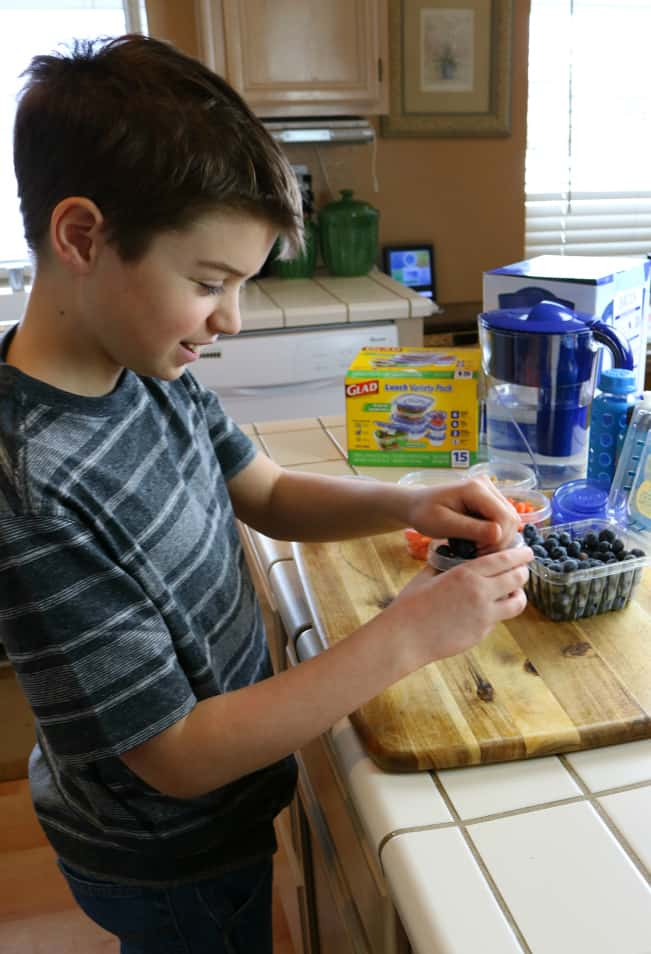 Son filling Glad containers with healthy snacks for kids