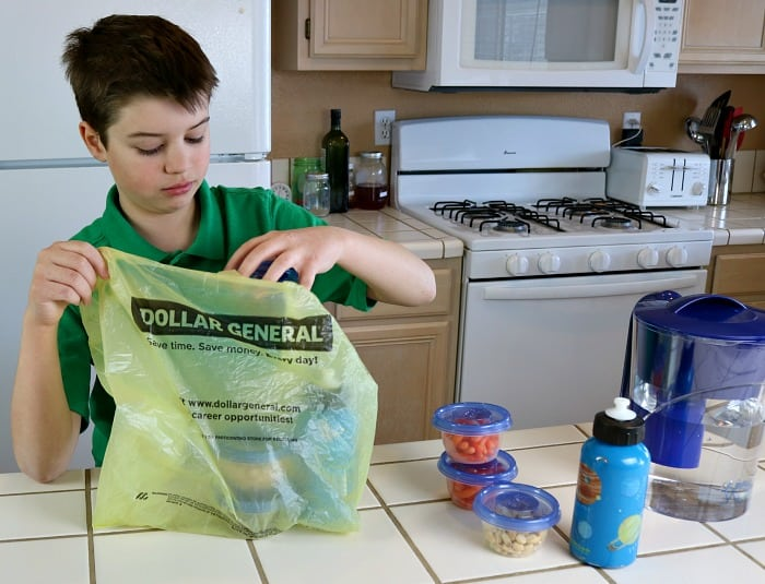 Son placing snacks and water bottles in a Dollar General grocery bag