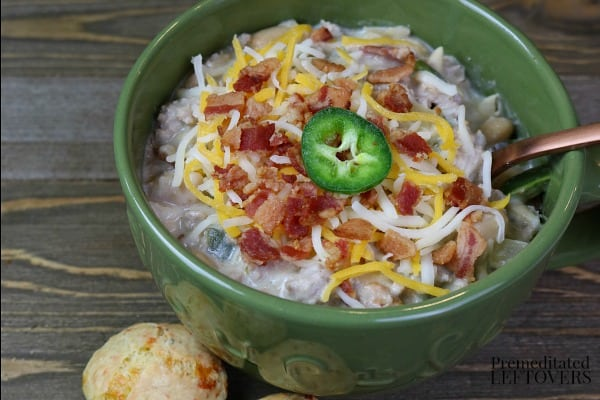 jalapeno popper chili in a green bowl topped with bacon and cheese