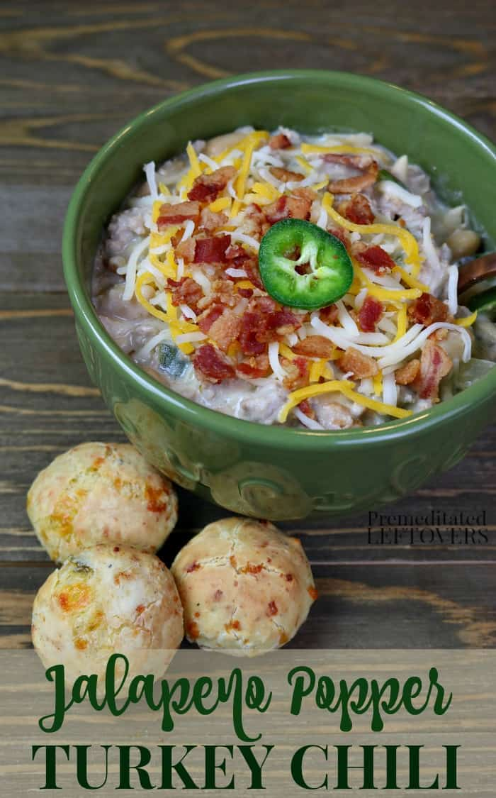 A bowl of jalapeno popper turkey chili topped with Monterrey Jack and Cheddar cheese, crumbed bacon, and a slice of jalapeno pepper.