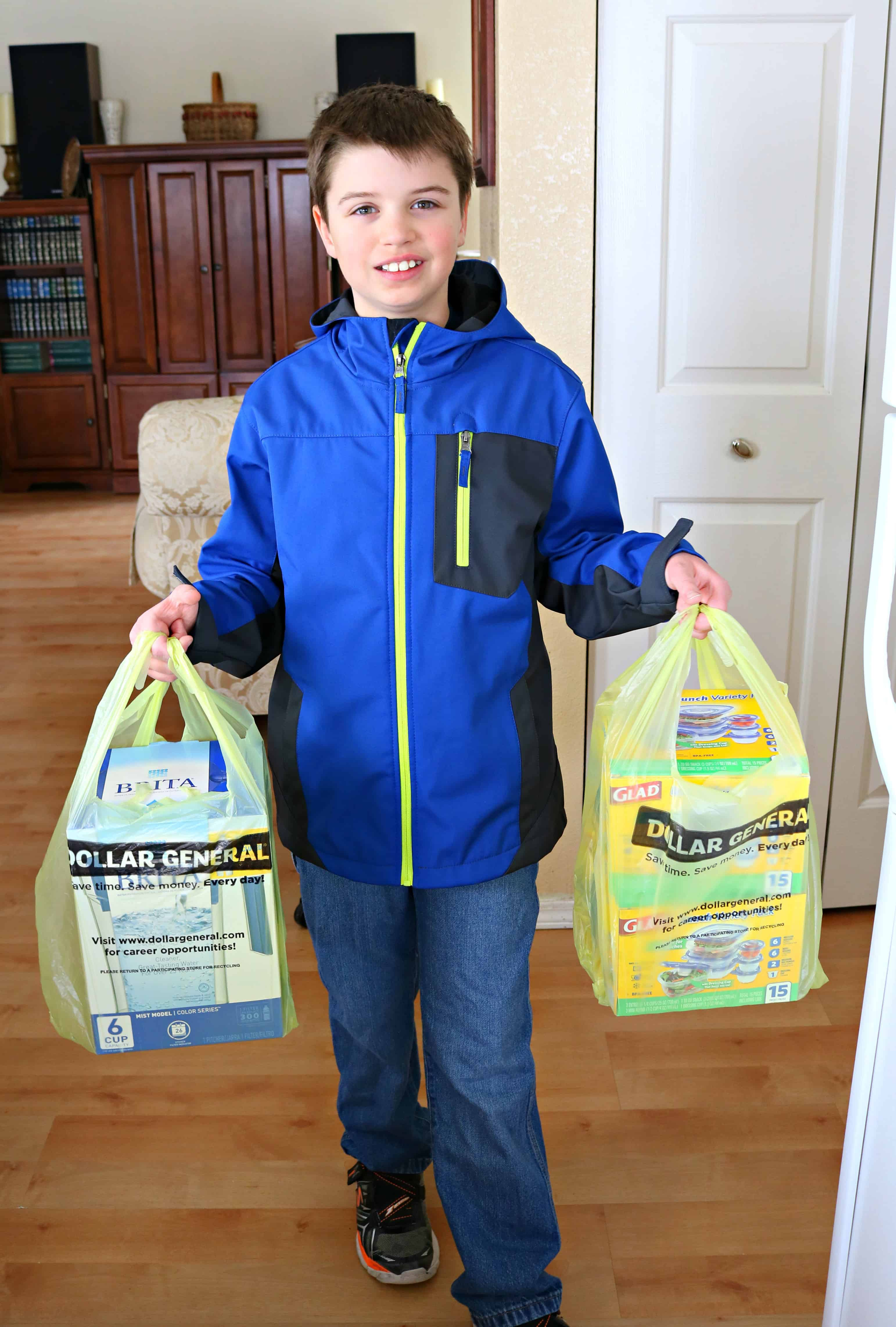 Young boy bringing in grocery bags from Dollar General