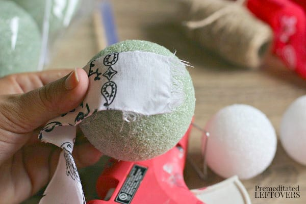 Place a dab of glue on the foam ball and then attach the fabric strip.