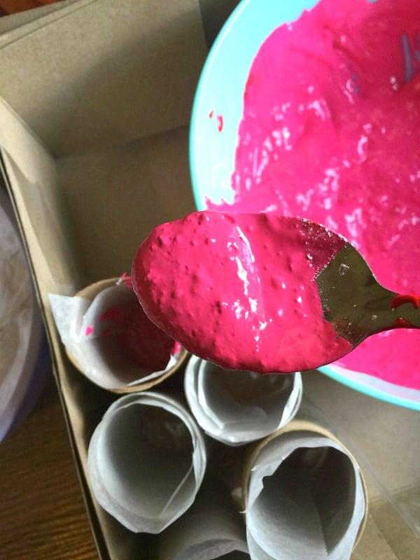 Spooning chalk mix into toilet paper tubes to make firecracker sidewalk chalk.