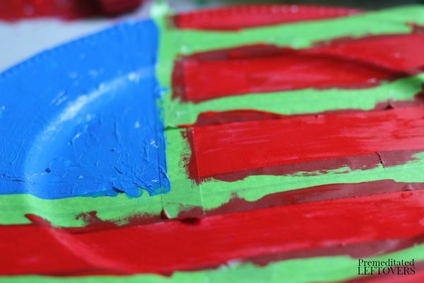 Use painters tape and star stickers to mark off white sections sections then paint it red and blue to create your patriotic flag chargers.