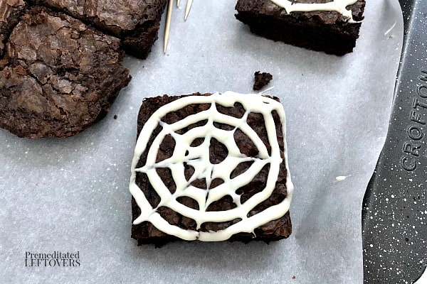 Use a toothpick and run it through the spiral of vanilla frosting to create a spider web on top of each brownie square