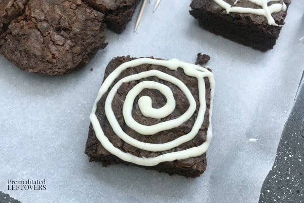 Use vanilla frosting to make a spiral on top of brownies to make spider web brownies