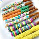 Easter white chocolate covered pretzel rods decorated with sprinkles on a platter