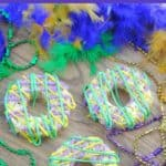 Purple, and green king cake rice krispie treats on a tray with a boa