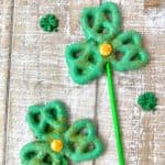 Shamrock pretzel pops covered in green candy melts with gold sprinkles