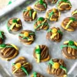 st patricks day pretzel turtles on a silver pan with colored candy drizzle