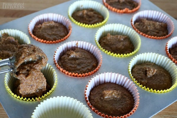 Putting gluten-free sweet potato muffin batter in muffin cups with cookie dough scoop.