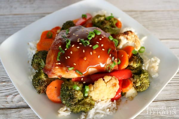 Sheet pan Mongolian chicken and vegetables recipe served over rice on a white plate.