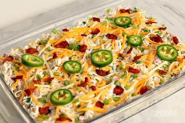 jalapeno popper chicken casserole topped with cheese and jalapeno slices