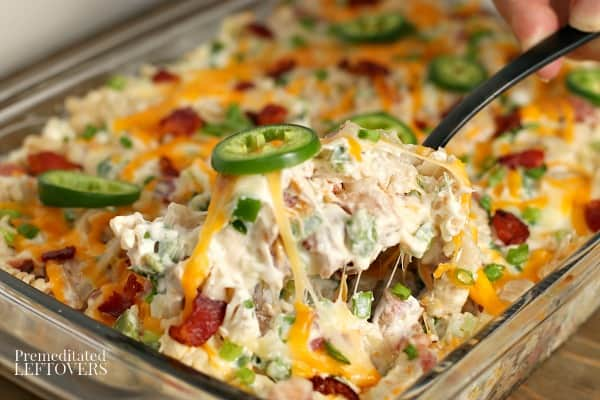 A serving spoon scooping out the jalapeno popper chicken casserole.