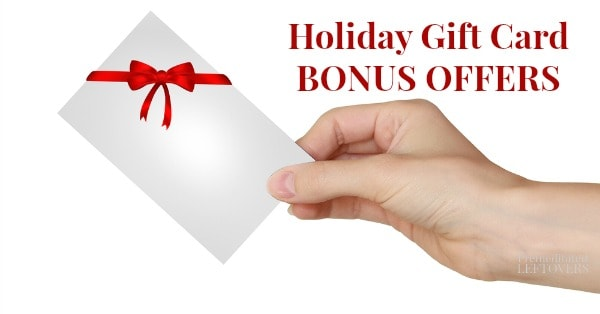 Hand holding gift card with red ribbon and bow for holiday bonus gift card offers